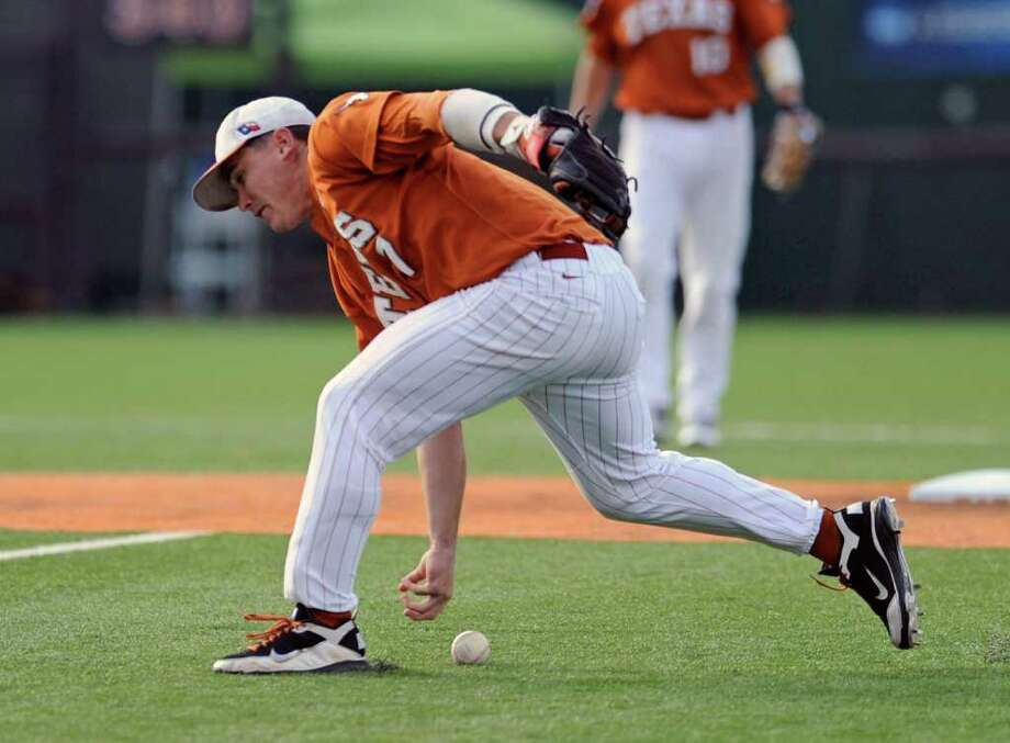 Texas second baseman Jordan Etier tries to barehand a groundball against Arizona State in June. UT dismissed Etier from its team Monday, two days after he was arrested and charged with evading arrest and possession of marijuana, both misdemeanors. Photo: Michael Thomas/Associated Press