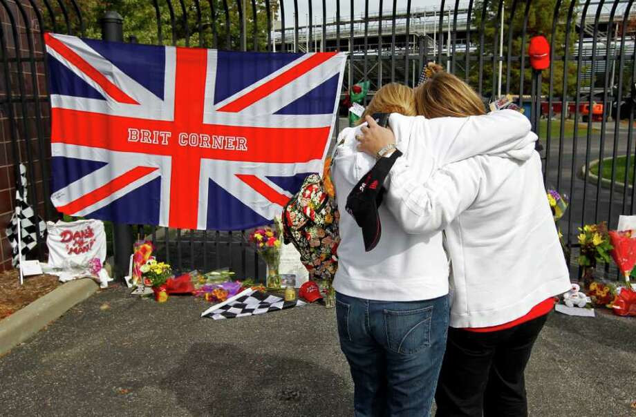 Helen McDonald, right, and Karen Edney hug as they visit a memorial at the main gate at the Indianapolis Motor Speedway for race driver Dan Wheldon in Indianapolis, Monday, Oct. 17, 2011. Wheldon, a two-time Indianapolis 500 champion, died Sunday after a massive, fiery wreck at the Las Vegas Indy 300.  (AP Photo/Michael Conroy) Photo: Michael Conroy
