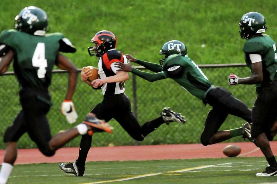 Mohonasen's C.J. Stone (33), center, shakes off Green Tech's Jamel Price (8) before running in for a touchdown during their football game on Friday, Sept. 2, 2011, at Union College in Schenectady, N.Y. (Cindy Schultz / Times Union) Photo: Cindy Schultz / 00014475A