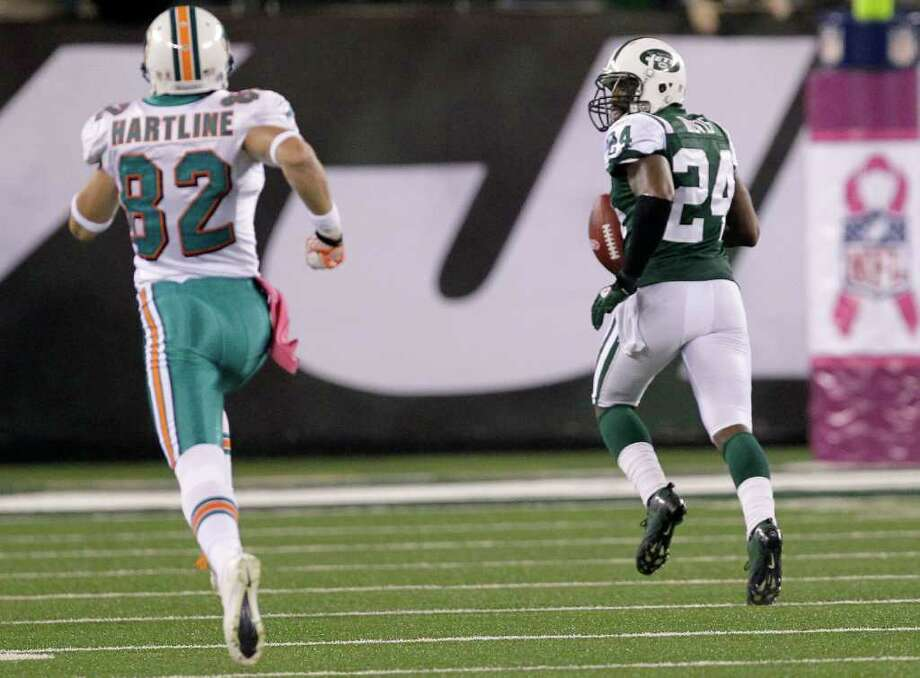 New York Jets cornerback Darrelle Revis (24) looks back at Miami Dolphins wide receiver Brian Hartline (82) as he returns an interception 100 yards for a touchdown during the first quarter of an NFL football game Monday, Oct. 17, 2011, in East Rutherford, N.J. (AP Photo/Julio Cortez) Photo: Julio Cortez