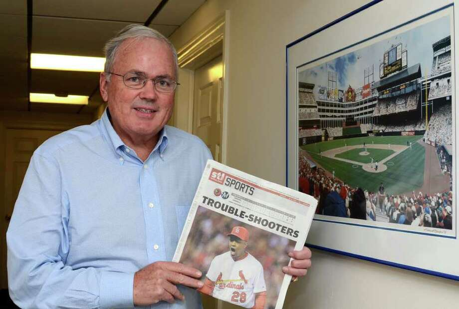 Craig Roberts Stapleton poses next to a framed photograph of Rangers Ballpark in Arlington while holding the front sports page of Sunday's STLToday newspaper featuring the Cardinals in his office at 315 East Putnam Avenue in Greenwich on Monday, Oct. 17, 2011. Stapleton co-owned the Texas Rangers baseball team with George W. Bush and in July 2009, he became a co-owner of the St. Louis Cardinals. Photo: Amy Mortensen, Greenwich Time / Greenwich Time