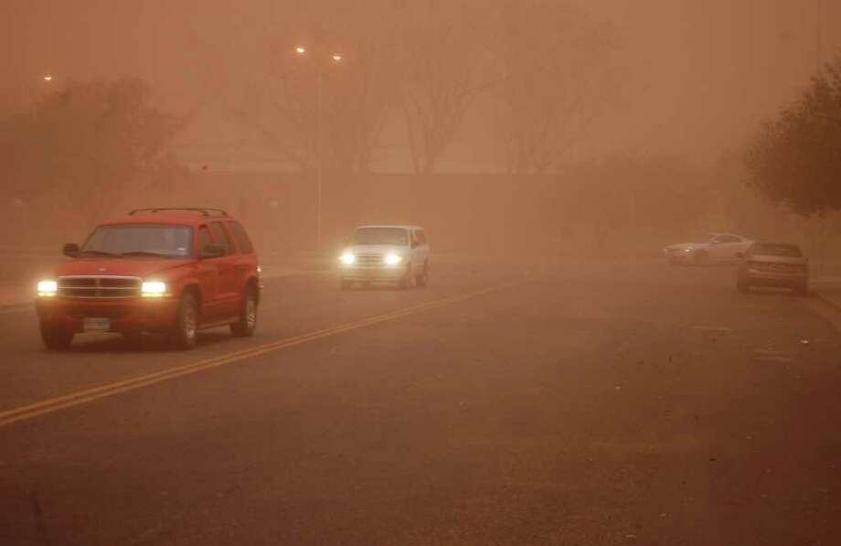 Traffic moves through a dust storm which cast a brown pall over downtown Lubbock, Texas on Monday, Oct. 17, 2011. A strong cold front bringing north and west winds gusting to 60 mph churned up the dust storm that roiled through the Texas South Plains. Photo: AP