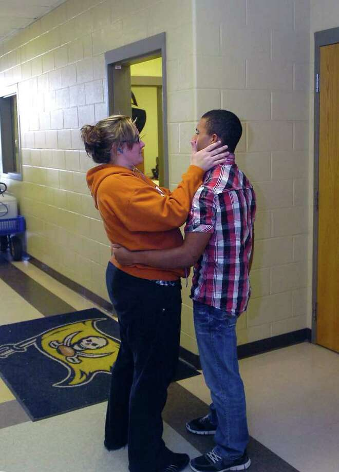Katherine Comeaux, left, offers condolences to Celly Thomas, the brother of varsity football player Matt Thomas outside the team lockerroom Monday morning. Vidor High School football players are grieving the loss of their friend and teammate Matt Thomas who died Sunday after being hit by a train. The school district was allowing the team to hang out Monday in the field house to deal with their grief.  Dave Ryan/The Enterprise Photo: Dave Ryan