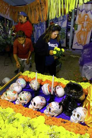 METRO/DAILY: Ernest Rejino,14, (L) Henry DeLeon (rear) and Esther Reyes (rt.) place mums on a day of the Dead Altar in Benavides Park Tuesday evening. The project was conducted by the San Antonio Housing Authority Cultural Arts Program as a part of their Public Housing Drug Elimination Program. Benavides Park is next to the Cassiano Homes. TO GO WITH JEANNE RUSSELL STORY. Staff Photo by: JOHN DAVENPORT Photo: JOHN DAVENPORT, JD / EN