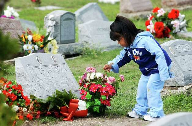 CONEXION: Two-year-old Raegan Ann London plays with flowers while at San Fernando cemetery with her great-grand parents on Thursday Nov. 2, 2006.   Helen L. Montoya/Staff Photo: HELEN L. MONTOYA, SAN ANTONIO EXPRESS-NEWS / SAN ANTONIO EXPRESS-NEWS