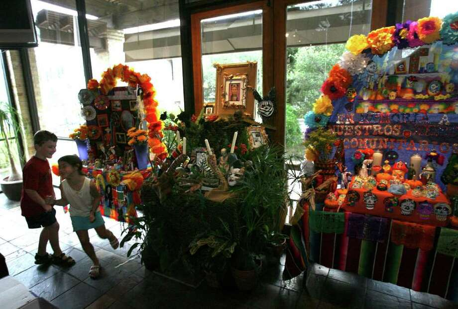 Samuel Delmer, 6, and katarina Gallardo, 6, play at Paloma Blanca restaurant.  Students, teachers and parents construct altars at Paloma Blanca restaurant in Alamo Heights for Dia de los Muertos between students from Cambridge Elementary, St. Peters Prince of the Apostles Elementary and Woodridge Elementary.  Saturday October 7, 2006.     (Robert McLeroy/San Antonio Express-News) SECONDARY PHOTO Photo: ROBERT MCLEROY, SAN ANTONIO EXPRESS-NEWS / San Antonio Express-News