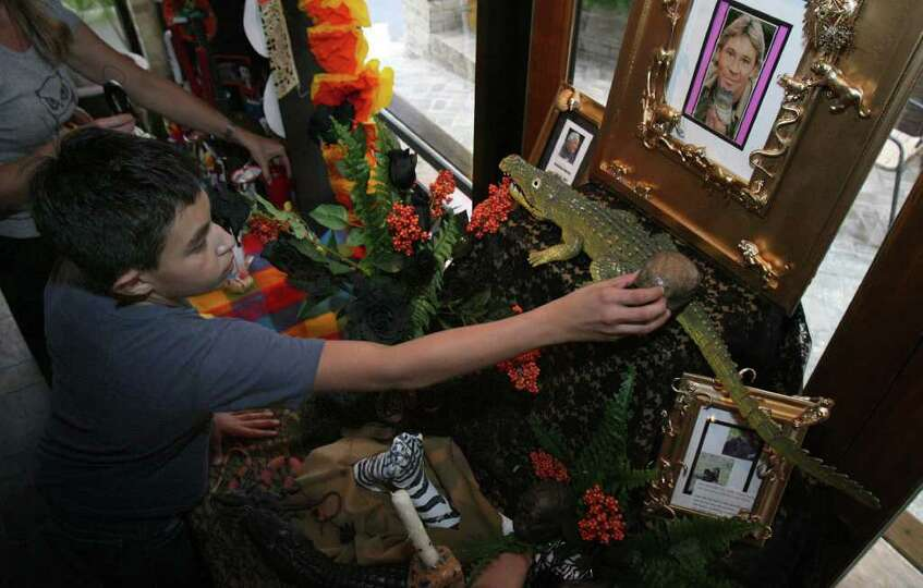 Eric Garcia, 14, adds a piece to an altar dedicated to Steve Erwin.  Eric's brother attends  St. Pet
