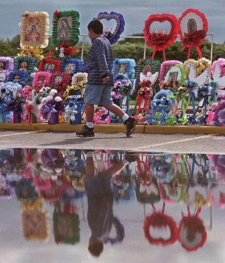 Jonathan Villa, 10, walks past a display of decorations set-up outside San Fernando Cemetery Sunday