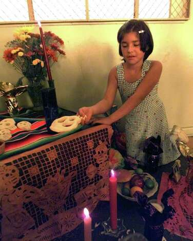 Daily Metro.  Priscilla Ochoa, 10, places a mask of her own creation on the altar of the Dia De Los Muertos festivities at the Southside Outreach Center.  Photo by Tom Reel  10/23/98 Photo: Trmuertos3.jpg