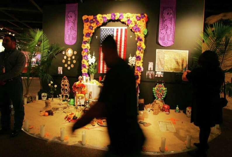 Families look at a Dia de los Muertos altar dedicated to fallen soldiers following a military recogn