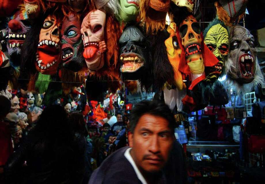 FOR METRO - A man makes his way past mask Sunday Oct. 30, 2005 in the 20 de Noviembre Mercado in Oaxaxa City, Oaxaca, Mexico during Dia De Los Muertos celebrations. PHOTO BY EDWARD A. ORNELAS/STAFF Photo: EDWARD A. ORNELAS, SAN ANTONIO EXPRESS-NEWS / SAN ANTONIO EXPRESS-NEWS