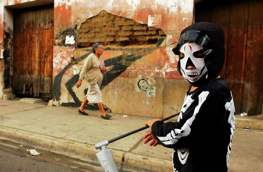 A boy in costume walks through the streets of Oaxaca City, Oaxaca, Mexico Friday Oct. 28, 2005 during Dia De Los Muertos celebrations.  Photo: EDWARD A. ORNELAS, SAN ANTONIO EXPRESS-NEWS / SAN ANTONIO EXPRESS-NEWS
