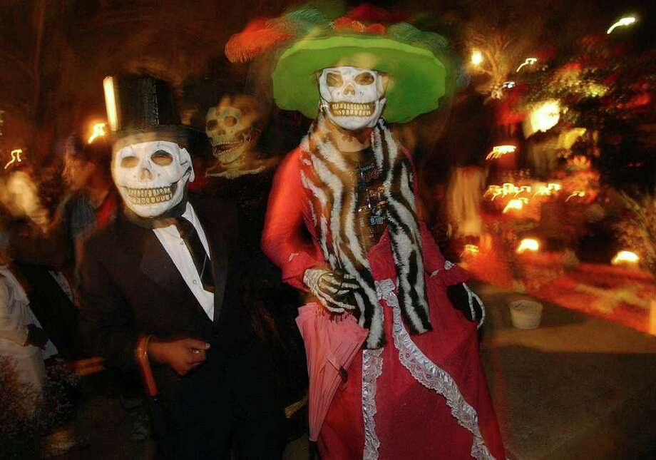 Teenagers dressed as catrines meander Monday Oct. 31, 2005 through the Panteon Municipal in Xoxocotlan, Oaxaca, Mexico during Dia De Los Muertos celebrations.  Photo: EDWARD A. ORNELAS, SAN ANTONIO EXPRESS-NEWS / SAN ANTONIO EXPRESS-NEWS