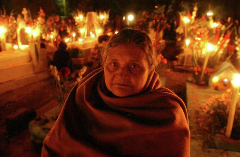 Casia Diaz Garcia sits near the grave of her husband Monday Oct. 31, 2005 at the Panteon Municipal in Xoxocotlan, Oaxaca, Mexico during Dia De Los Muertos celebrations.  Photo: EDWARD A. ORNELAS, SAN ANTONIO EXPRESS-NEWS / SAN ANTONIO EXPRESS-NEWS