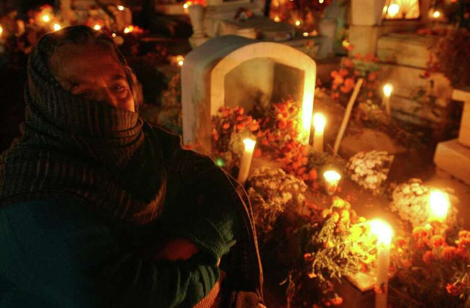 Porfiria Matias Canseco sits at the grave of her parents Monday Oct. 31, 2005 at the Panteon San Sebastian in Xoxocotlan, Oaxaca, Mexico during Dia De Los Muertos celebrations.  Photo: EDWARD A. ORNELAS, SAN ANTONIO EXPRESS-NEWS / SAN ANTONIO EXPRESS-NEWS