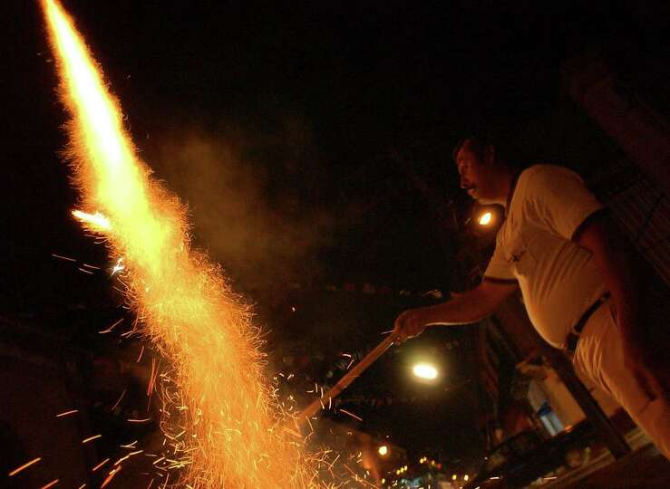 A man lights fireworks on the streets of Oaxaxa City, Oaxaca, Mexico during Dia De Los Muertos celeb