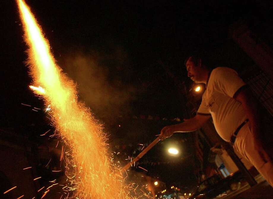 A man lights fireworks on the streets of Oaxaxa City, Oaxaca, Mexico during Dia De Los Muertos celebrations Friday Oct. 28, 2005. Photo: EDWARD A. ORNELAS, SAN ANTONIO EXPRESS-NEWS / SAN ANTONIO EXPRESS-NEWS