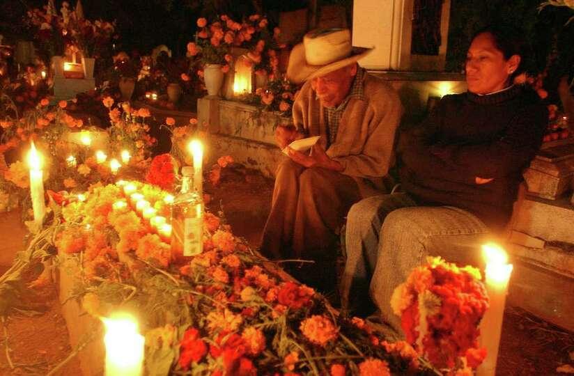Maria Magdalena Garcia Garcai and her dad Vicente Paolino sit at a relatives grave Tuesday Nov. 1, 2