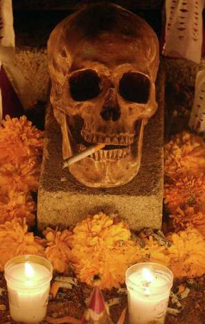 FOR METRO - A calavera rests on a grave Monday Oct. 31, 2005 in the Panteon Municipal in Xoxocotlan, Oaxaca, Mexico during Dia De Los Muertos celebrations. PHOTO BY EDWARD A. ORNELAS/STAFF Photo: EDWARD A. ORNELAS, SAN ANTONIO EXPRESS-NEWS / SAN ANTONIO EXPRESS-NEWS