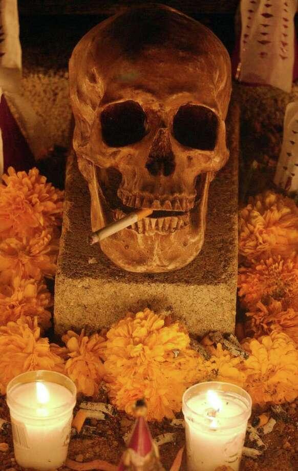 A calavera rests on a grave Monday Oct. 31, 2005 in the Panteon Municipal in Xoxocotlan, Oaxaca, Mexico during Dia De Los Muertos celebrations.  Photo: EDWARD A. ORNELAS, SAN ANTONIO EXPRESS-NEWS / SAN ANTONIO EXPRESS-NEWS
