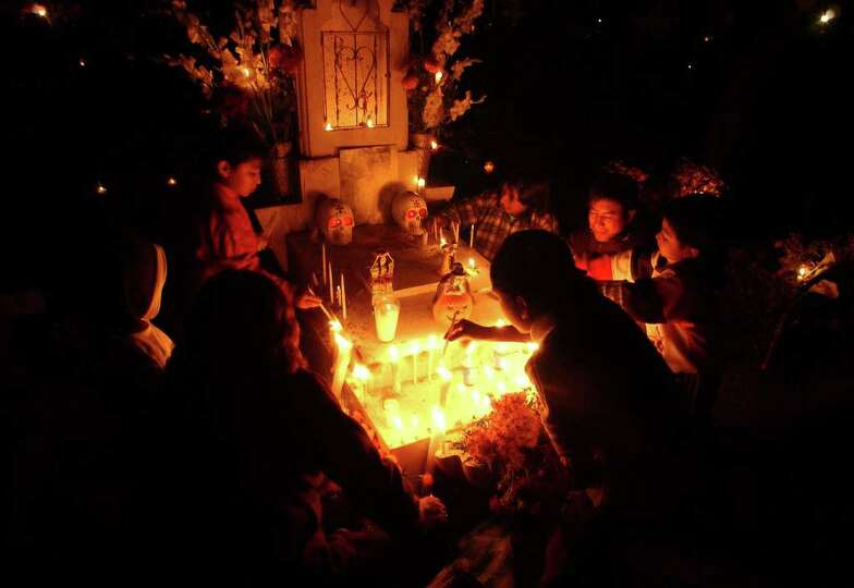 A family gathers around the grave of relatives Monday Oct. 31, 2005 in the Panteon Municipal in Xoxo