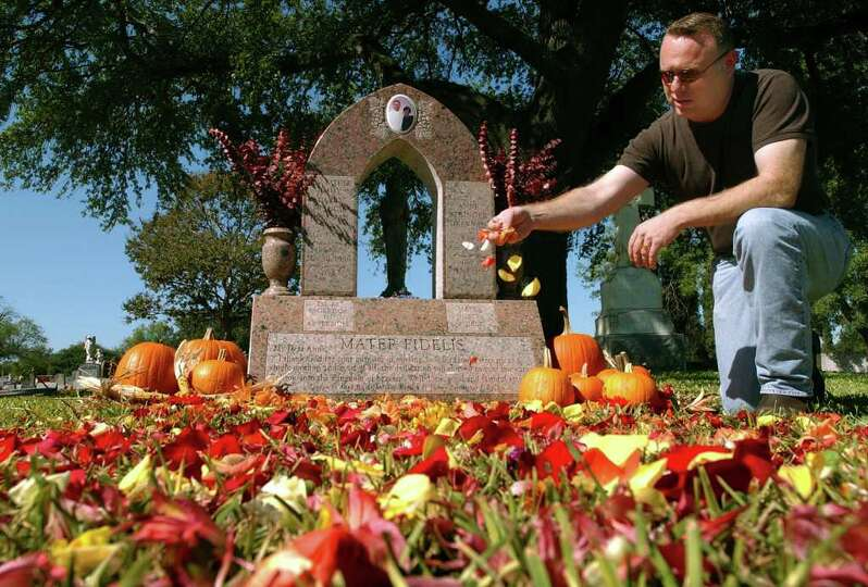Fr. Jimmy Drennan spreads flower petals on his beloved mother's grave at San Fernando Cemetary #2, T