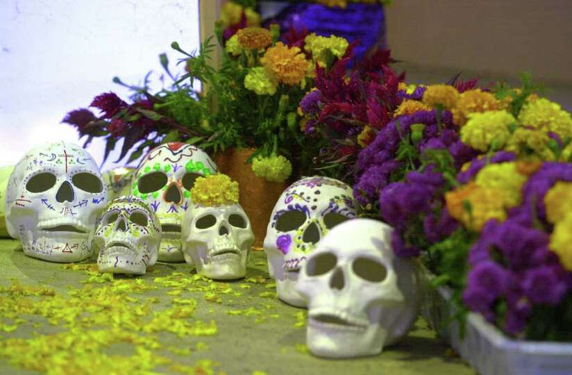 Decorated sculls and flowers lie at the base of a community altar Friday, November 2, 2001 at Inman