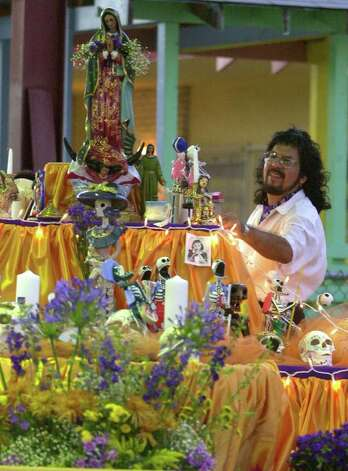 NBR WS DIA DE LOS MUERTOS - Nephtali de Leon looks over a community altar Friday,  November 2, 2001 at Inman Christian Center. Community members were urged to contribute photos and items of loved ones to the Dia de los Muertos altar. BAHRAM MARK SOBHANI/STAFF