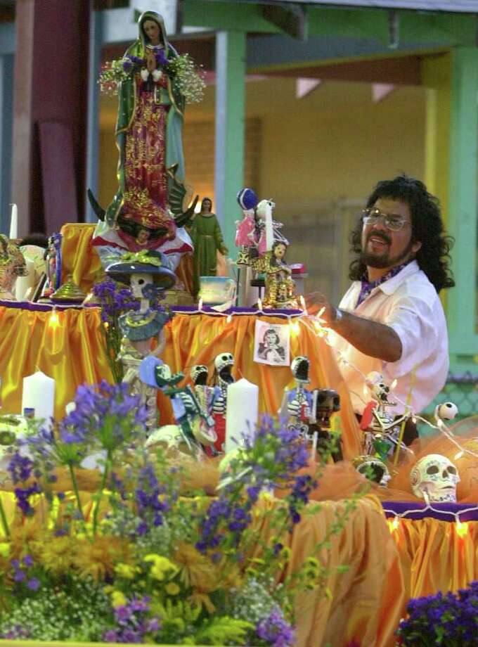 Nephtali de Leon looks over a community altar Friday,  November 2, 2001 at Inman Christian Center. Community members were urged to contribute photos and items of loved ones to the Dia de los Muertos altar. BAHRAM MARK SOBHANI/STAFF
