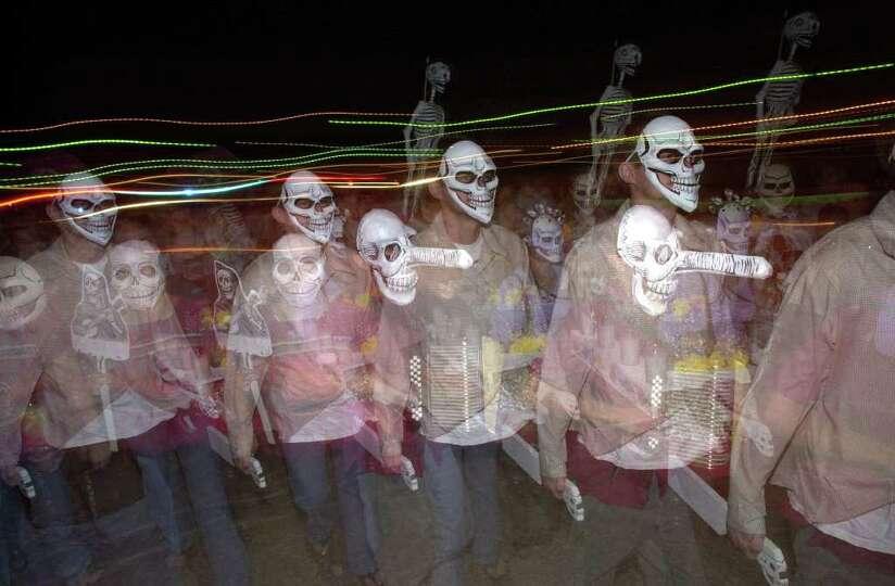 A Dia de los Muertos processional walks toward the Guadalupe Cultural Arts Center's Visual Arts Anne