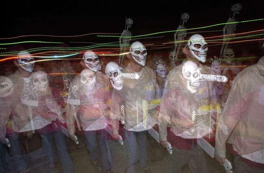 A Dia de los Muertos processional walks toward the Guadalupe Cultural Arts Center's Visual Arts Annex Thursday, November 1, 2001. BAHRAM MARK SOBHANI/STAFF Photo: BAHRAM MARK SOBHANI, SAN ANTONIO EXPRESS-NEWS