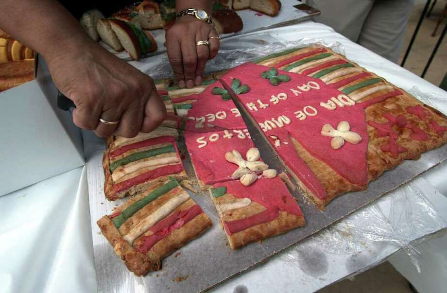 Pan de los Muertos is cut for people to eat at the conclusion of Our Lady of the Lake's Dia de los Muertos event on November 1, 2001. Kin Man Hui/staff. Photo: KIN MAN HUI, EXPRESS-NEWS / EXPRESS-NEWS