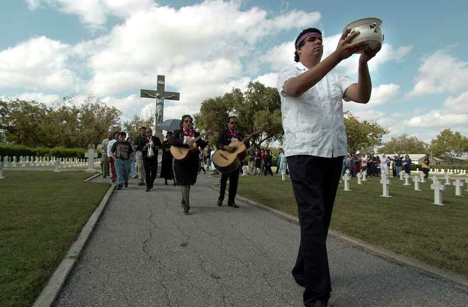 Our Lady of the Lake professor Oswald John Nira (left) leads a procession of Dia de los Muertos on the university grounds on Thursday, November 1, 2001.  Photo: KIN MAN HUI, EXPRESS-NEWS / EXPRESS-NEWS