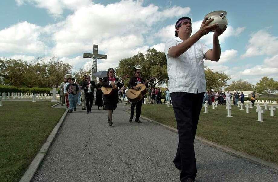 Our Lady of the Lake professor Oswald John Nira (left) leads a procession of Dia de los Muertos on the university grounds on Thursday, November 1, 2001.  Photo: KIN MAN HUI, EXPRESS-NEWS / EXPRESS-NEWS