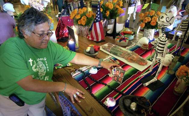 SA Life adv - Enedina Vasquez works on an altar for the Dia de los Muertos, at Market Square, dedicated to those who perrished in the attack on the World Trade Center, Saturday, Oct. 27, 2001.  photo bob owen Photo: BOB OWEN, SAN ANTONIO EXPRESS-NEWS