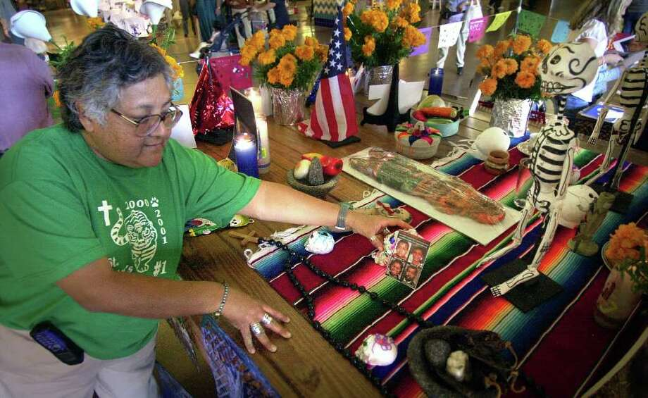 Enedina Vasquez works on an altar for the Dia de los Muertos, at Market Square, dedicated to those who perrished in the attack on the World Trade Center, Saturday, Oct. 27, 2001.  Photo: BOB OWEN, SAN ANTONIO EXPRESS-NEWS
