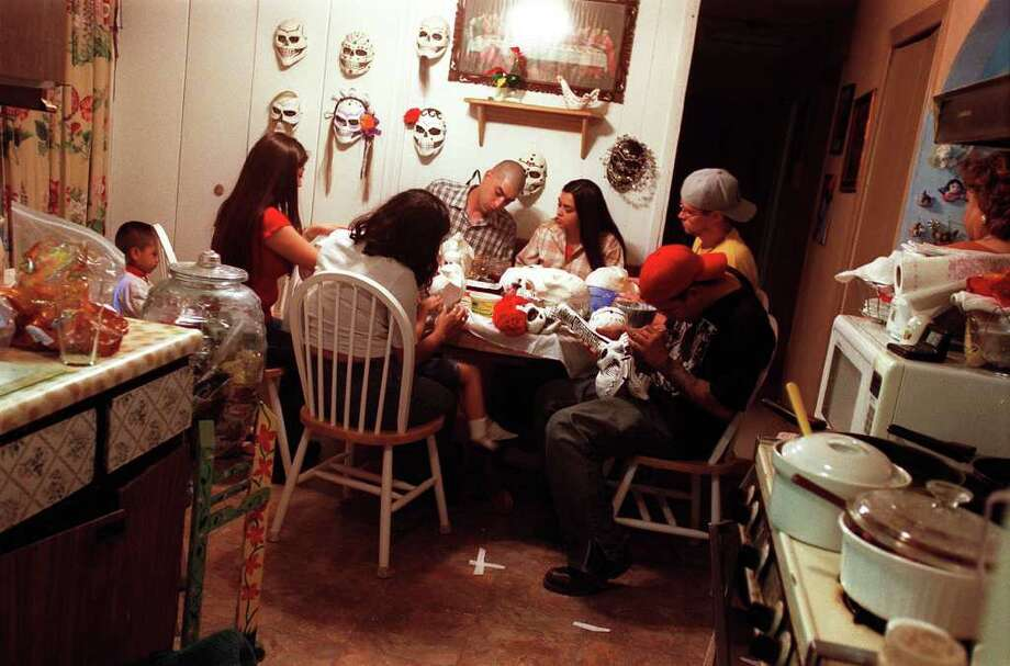 Brothers and sisters, aunts and uncles, nieces and nephews, and granchildren all gather in Imelda Garcia's kitchen to participate in the The Garcia family tradition of making calaveras masks for Dia de Los Muertos. Photo: ANITA BACA, EN / EN