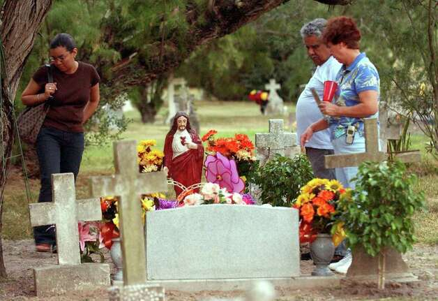STATE/DAILY/ DIA DE LOS MUERTOS:(L-R) Corin Cruz and her parents Santos P. Cruz and Rita visit the cemetary  where her grandparents are buried during the 1st annual Day of the Dead Celebration at the Harlingen Cemetary Nov.1, 2004. DELCIA LOPEZ/STAFF Photo: DELCIA LOPEZ, SAN ANTONIO EXPRESS NEWS / SAN ANTONIO EXPRESS NEWS