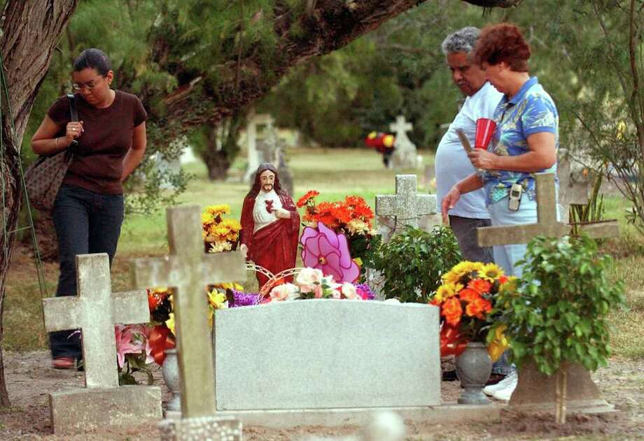 Corin Cruz and her parents Santos P. Cruz and Rita visit the cemetary  where her grandparents are buried during the 1st annual Day of the Dead Celebration at the Harlingen Cemetary Nov.1, 2004.  Photo: DELCIA LOPEZ, SAN ANTONIO EXPRESS NEWS / SAN ANTONIO EXPRESS NEWS