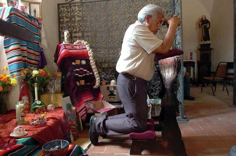 Severiano Casarez prays by an