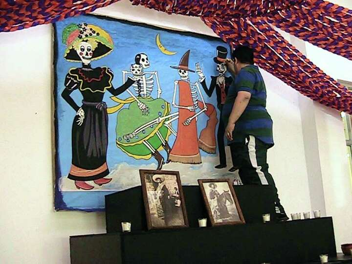 Un empleado municipal da los últimos detalles al mural que por el Día de Muertos transforma una de