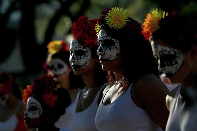METRO - Dancers with Austin Samba School watch the Las Monas Drum and Dance group perform during the Dia de los Muertos celebration at La Villita on Sunday, Nov. 1, 2009. LISA KRANTZ/lkrantz@express-news.net Photo: LISA KRANTZ, SAN ANTONIO EXPRESS-NEWS / lkrantz@express-news.net