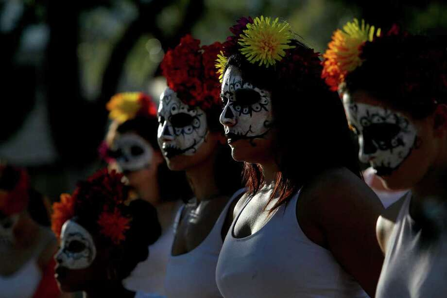 Dancers with Austin Samba School watch the Las Monas Drum and Dance group perform during the Dia de los Muertos celebration at La Villita on Sunday, Nov. 1, 2009. LISA KRANTZ/lkrantz@express-news.net Photo: LISA KRANTZ, SAN ANTONIO EXPRESS-NEWS / lkrantz@express-news.net