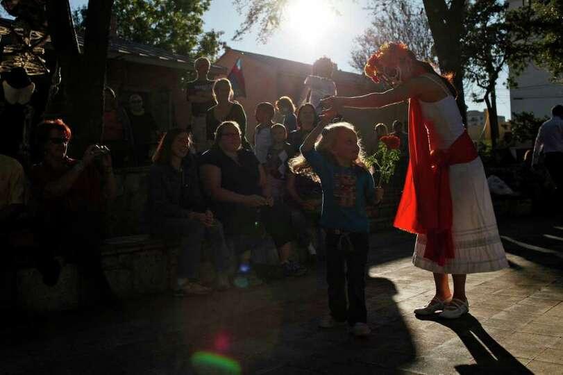 Magaly Medina, with Austin Samba School, twirls Peyton Owens, 4, during the Dia de los Muertos celeb