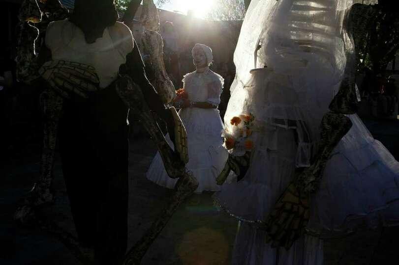Miranda Key, center, particpates in the Dia de los Muertos celebration at La Villita with Leif and L