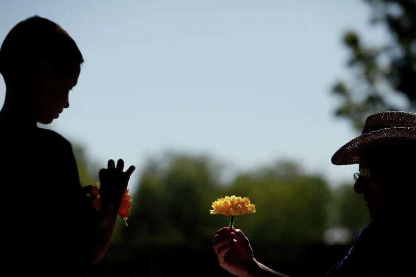Joseph Schumacher, 12, left, makes a paper marigold with the help of volunteer Mario Gonzalez at the