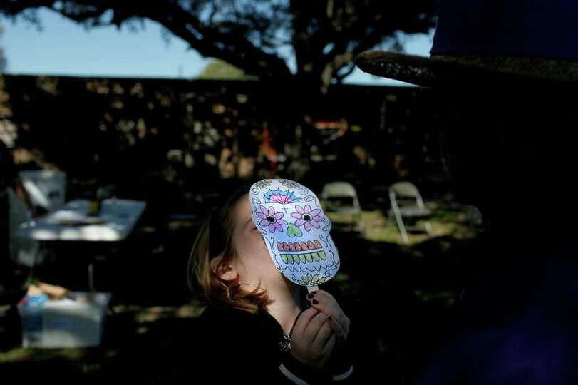 METRO -- Karalyn Roach, 7, shows off the mask she made to volunteer Nancy Curry during the San Anton