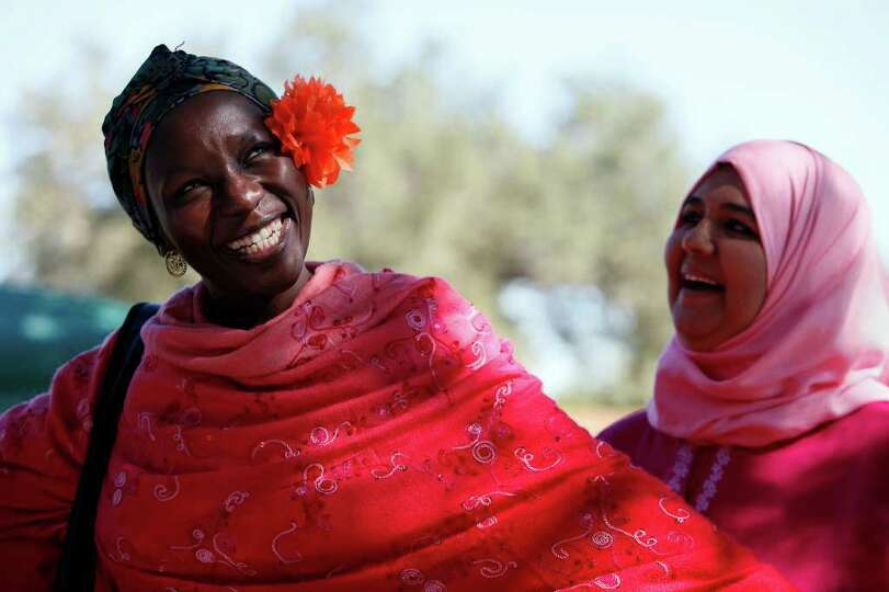 Magajiya Usman, left, of Nigeria, and Hawa Almeer, of Bahrain, laugh after Usman put a paper marigol