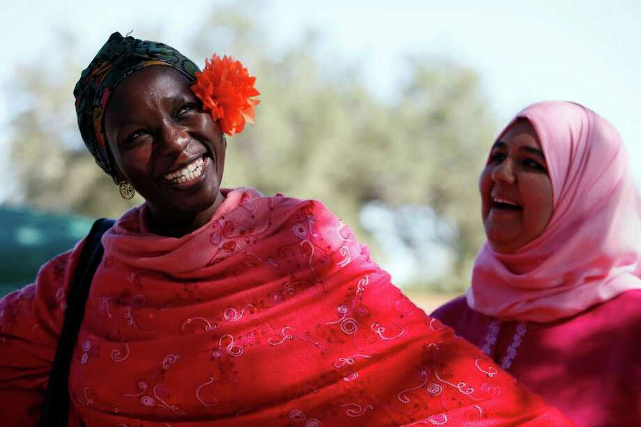Magajiya Usman, left, of Nigeria, and Hawa Almeer, of Bahrain, laugh after Usman put a paper marigold she made behind her ear during the San Antonio Missions National Historical Park's El Dia de los Muertos event at Mission San Jose on Sat, Oct. 31, 2009.  Photo: LISA KRANTZ, San Antonio Express-News / lkrantz@express-news.net