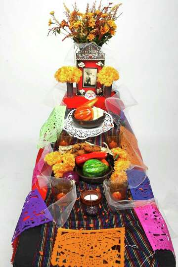 Thelma Muraida, a local instructor builds an altar ofrendas for Dia de los Muertos.  HELEN L. MONTOY